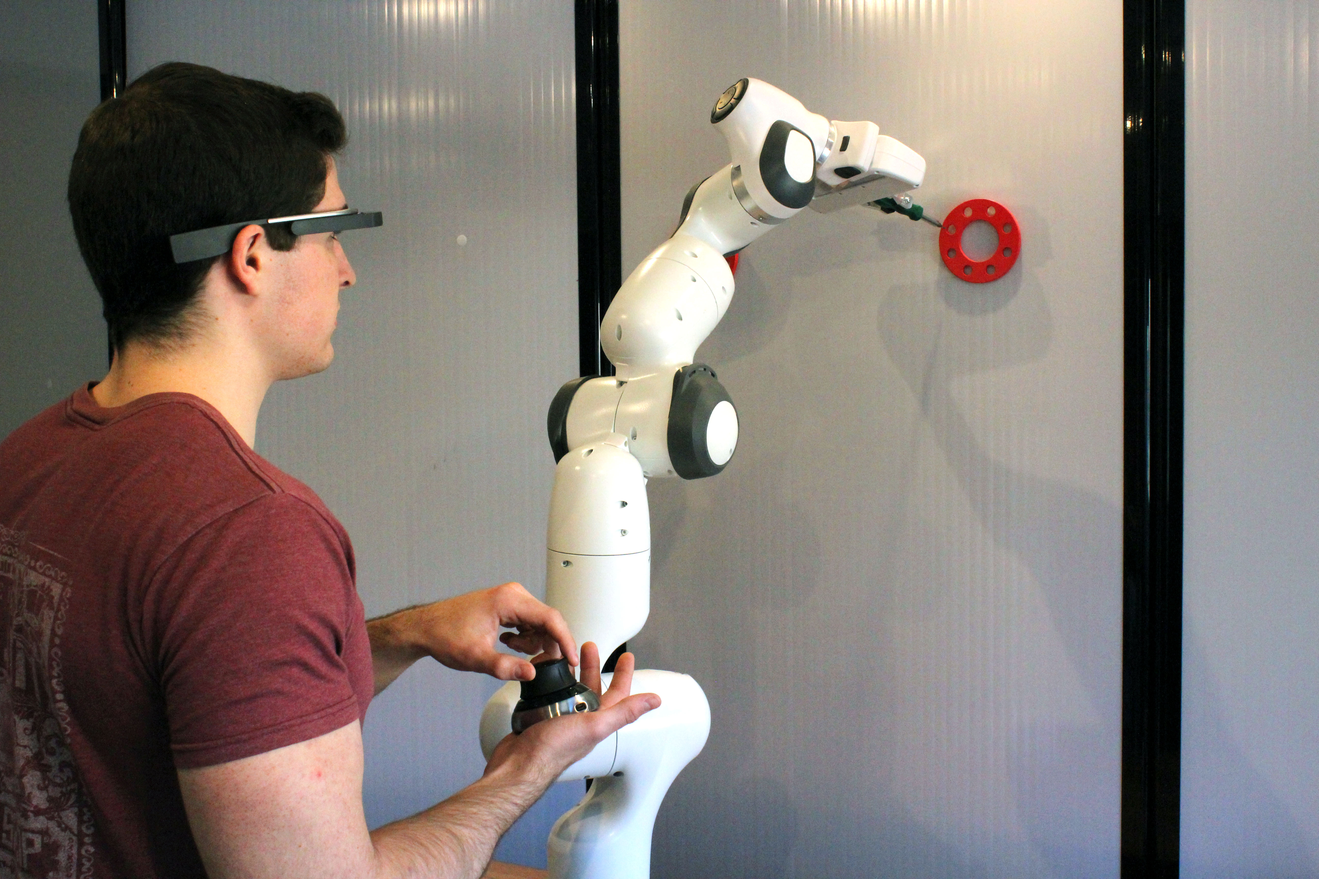 The research team's first prototype of its shared human-robot collaboration platform. An operator controls the arm to perform a representative task with assistance from a heads-up display.